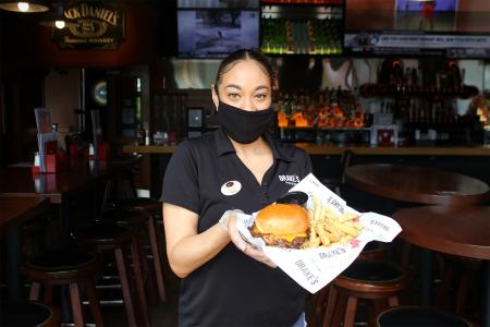 female server wearing a facemask and holidng a burger and fries at drake's florence, ky.