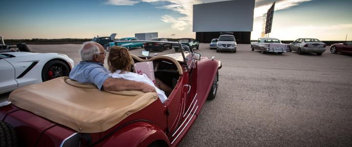 A couple sits in a vintage car in front of a movie screen at Stars & Stripes Drive-In Theater