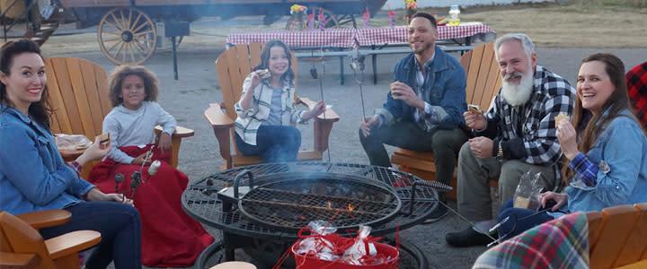 Visitors enjoy a campfire near the Conestoga wagon at the Orr Family Farm.