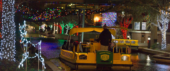 Bricktown Water Taxi  cruising through the water surrounded by winter lights