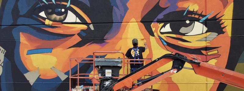 Image of artist on lift painting a mural of an African-American child's eyes.