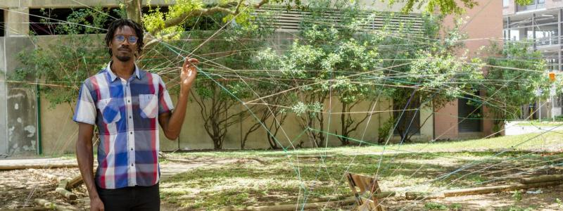 Image of Ronald Llewellyn Jones in one of his string sculptures constructed outdoors.