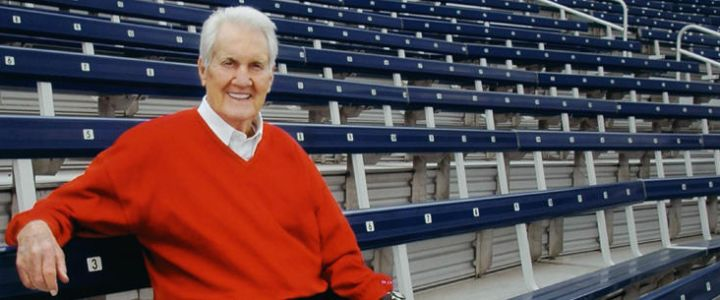 Pat Summerall sits on navy bleachers from Southern Bleacher Company