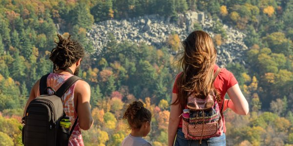 A young couple with a small child overlook fall scenery and rocks at Devil's Lake State Park.