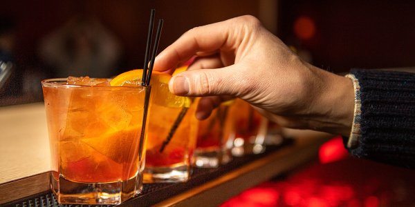 A line of Old Fashioned cocktails being made