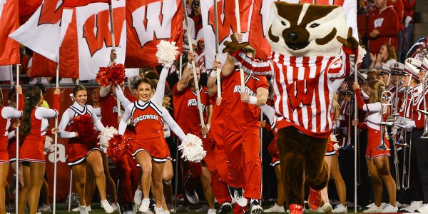 Bucky Badger runs out onto the field with cheerleaders prior to a game