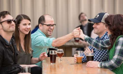 Friends handshaking over beers at an outdoor table at River Rat
