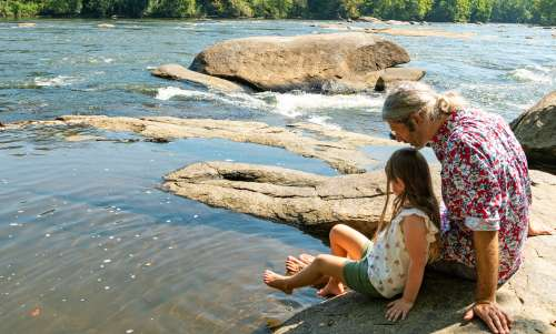 Father and daughter sitting on the banks of the Broad River