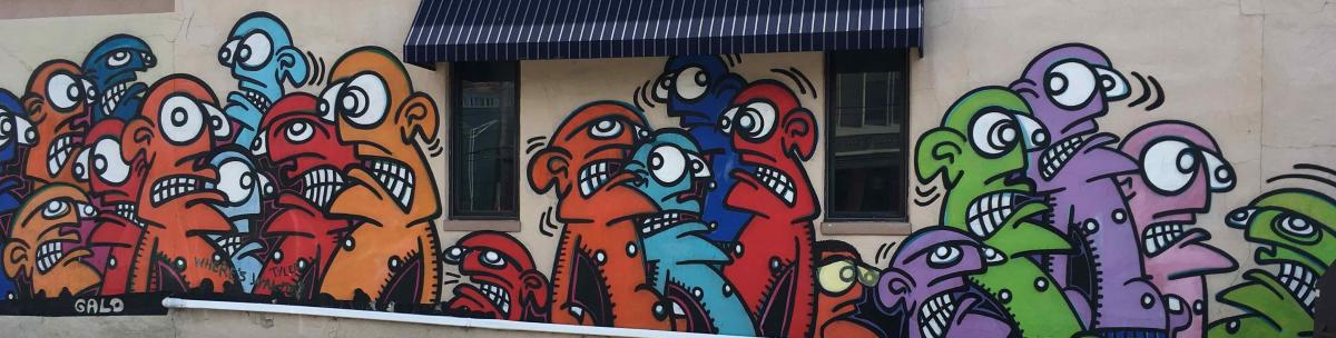 Street art in Covington, Ky. depicting multi-colored faces with big eyes by artist Galo.