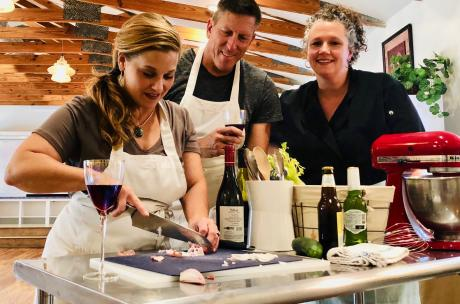 Friends drinking wine while taking a culinary cooking class