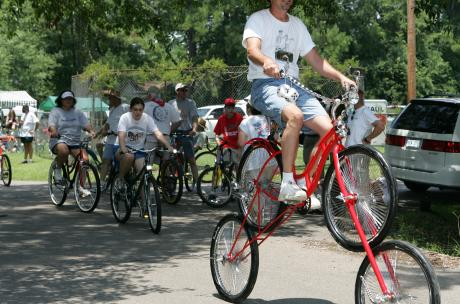 Man Riding 2 Bicycles at Once at Louisiana Bicycle Festival in Abita Springs