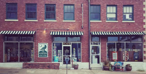 Exterior of the Raven Bookstore, with red brick walls and black and white striped awnings.
