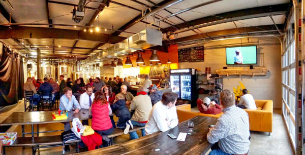 A crowd of people sit at long wooden tables at OMNI Brewing in Maple Grove, MN