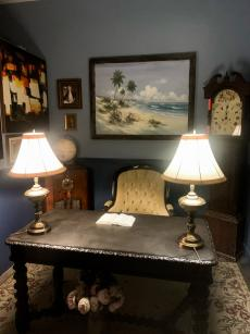 A dimly-lit room is filled with a wooden desk with two lamps on it, a regal desk chair, and art on the walls.