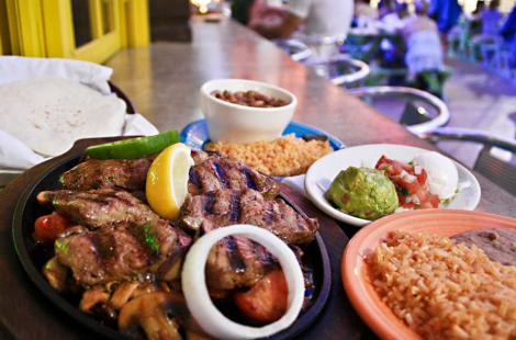 plate of steak with a lemon and side dishes of rice, beans, sour cream, guacamole and salsa at a the Blue Goose in Frisco, TX