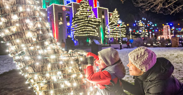 Kids and mom looking at a tree trunk wrapped in lights during the Snow Much Fun event