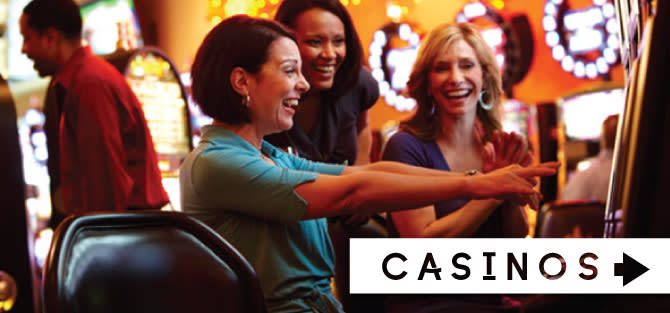 Three women smiling and laughing while playing games at a Northwest Indiana Casino
