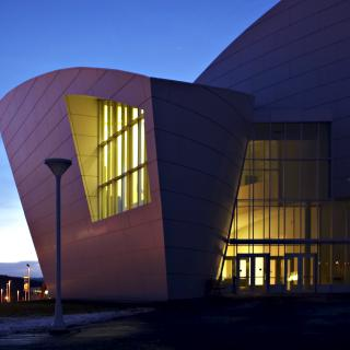An irregular shaped building at sunset with lighted glass front
