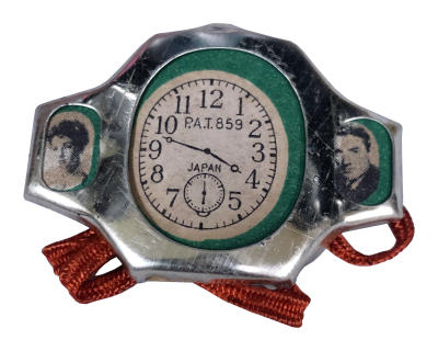 Toy watch with images of Elizabeth Taylor and Gregory Peck on either side of clock image.
