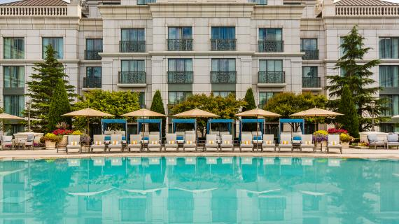 Pool side view of pool, lounge chairs, and hotel at the Grand America Hotel in Salt Lake City