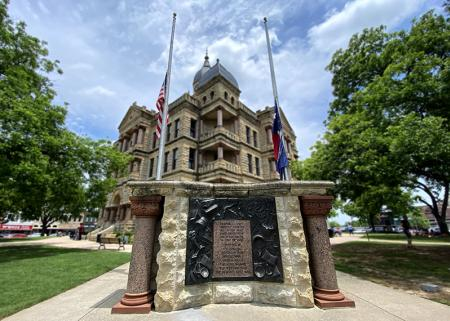 Denton County All War Memorial with Courthouse and flags in background