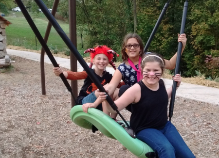 nature play at Behringer-Crawford Museum swing with three people on it