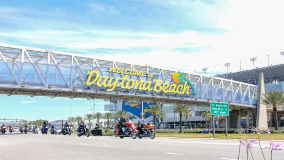 Motorcycle riders cruise under the Welcome to Daytona Beach sign at the Speedway under bright blue skies