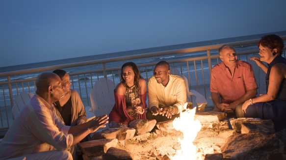 A group of friends enjoy the fire pit at an oceanfront beach bar in Daytona Beach