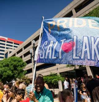 Man holding Pride Salt Lake Flag