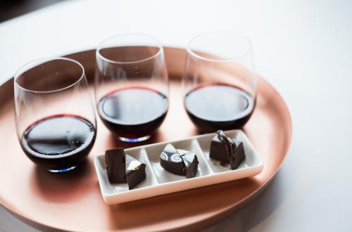 Three different glasses of wine paired with three different chocolates on a tray at Cocoa Dolce in Wichita