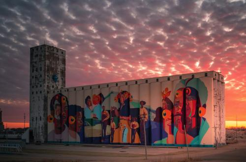 The Horizontes mural from a distance with a pink, orange, and purple sunset