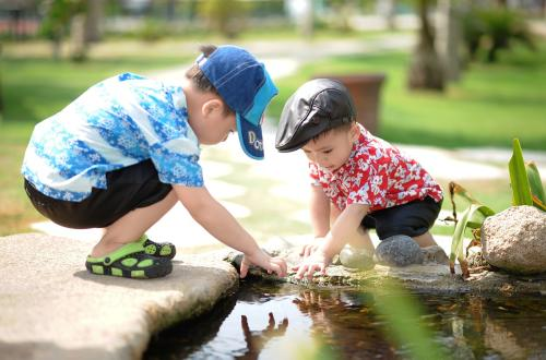 Two young boys play with rocks in a small pond