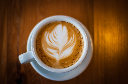 Beautiful coffee art displayed in the top of a latte shows a floral patter from Fairmount Coffee Shop in Wichita KS
