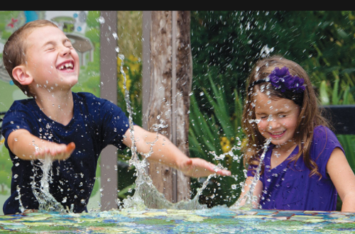 A boy and girl splash around in a puddle at Botanica in Wichita