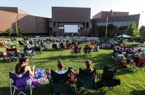 A crowd of people sit in lawnchairs on the lawn at the Wichita Art Museum for Tunes and Tallgrass