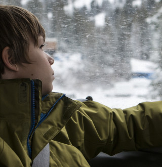 Boy Looking Out Window on His Way to Ski