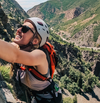 Girl Rock climbing with road and canyon behind her