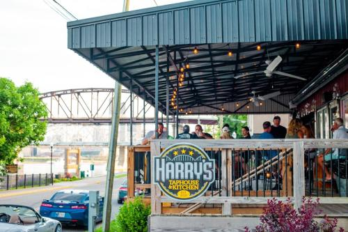 Exterior view of Harry's Taphouse with people sitting on the covered patio