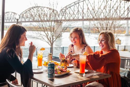 Three women eating and laughing at a patio table with an Ohio River bridge in the background.