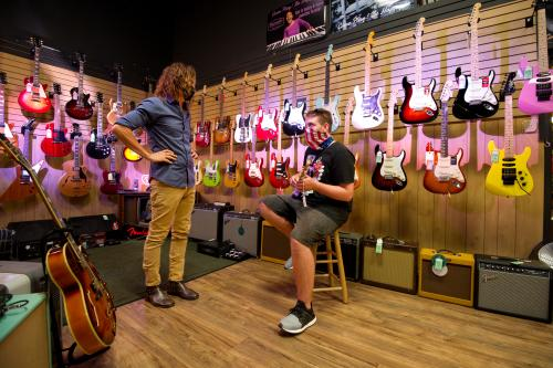 Two men with masks on chatting among guitars at Maxwell's House of Music