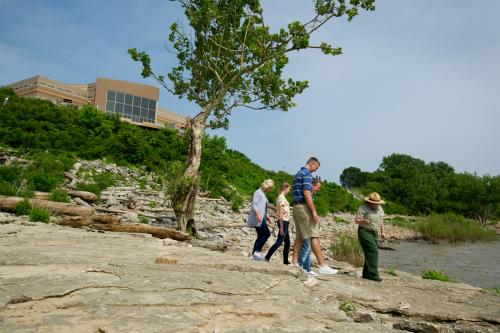 Family walking with the park ranger at Falls of the Ohio