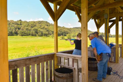 A woman shooting in a firing range while two men look on, at Sporting Club at The Farm.