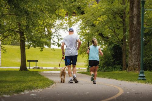Joggers with a dog on the Ohio River Greenway