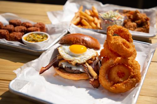 A burger served with onion rings, an apetitizer, fried chicken wings and french fries at Heartland Sports Pub in Elizabethtown Ky