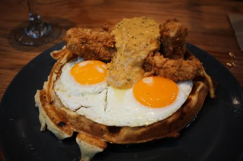 Chicken & Waffles Breakfast at Whiskey Cafe is topped with eggs, fried chicken and sausage gravy.