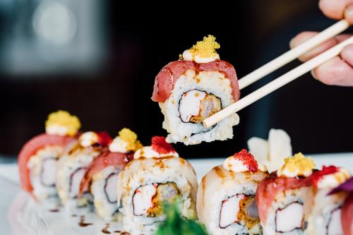 A patron enjoys a fresh sushi roll at eeZ Fusion in Huntersville, NC.