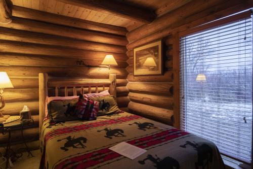 Cozy cabin interior with bed and a view, Vee Bar Guest Ranch, Laramie, Wyoming