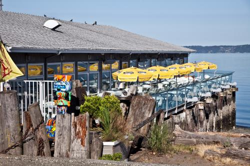 Salty's deck on Puget Sound with tables and yellow sun umbrellas