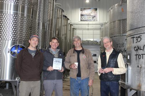 Staff from Sheldrake Point Winery Pose with the plaque awarding them the April 2021 Business of the Month Award.