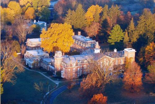 The Oneida Community Mansion House surrounded by vibrant fall colors, as seen from up in the air